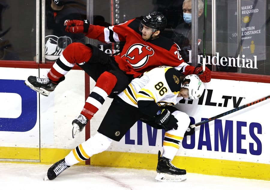 NEWARK, NEW JERSEY - JANUARY 14:  Michael McLeod #20 of the New Jersey Devils and Kevan Miller #86 of the Boston Bruins collide in the second period during the home opening game at Prudential Center on January 14, 2021 in Newark, New Jersey. (Photo by Elsa/Getty Images)