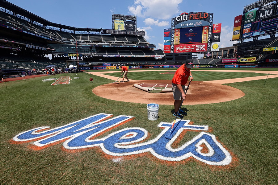 A grounds crew member paints the Mets logo on the field during the 84th MLB All-Star Game on July 16, 2013 at Citi Field in New York City. (Photo by Bruce Bennett/Getty Images)
