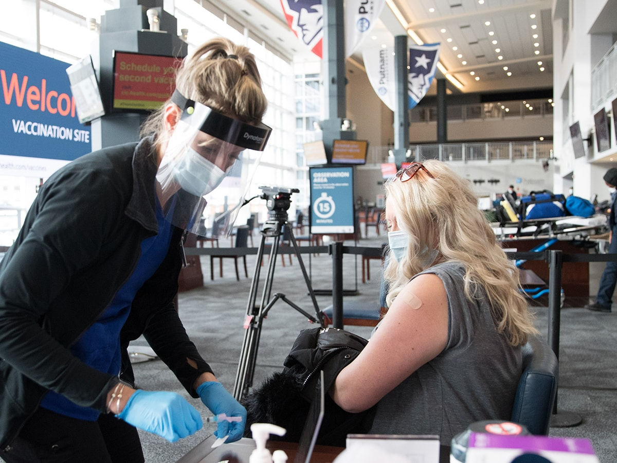 FOXBOROUGH, MA - JANUARY 15: A nurse with a woman following her COVID-19 vaccination at the Gillette Stadium vaccinations site on January 15, 2021. (Photo by Scott Eisen/Getty Images)