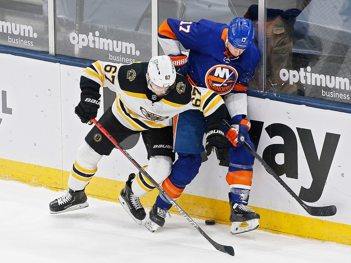 Mar 9, 2021; Uniondale, New York, USA; Boston Bruins defenseman Jakub Zboril (67) and New York Islanders left wing Matt Martin (17) battle for a loose puck during the first period at Nassau Veterans Memorial Coliseum. Mandatory Credit: Andy Marlin-USA TODAY Sports