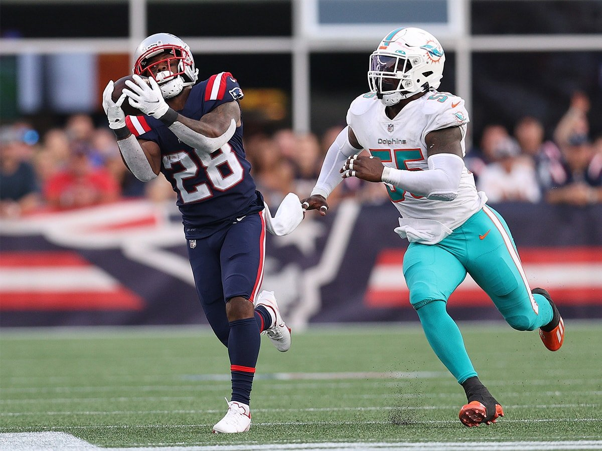 FOXBOROUGH, MASSACHUSETTS - SEPTEMBER 12: James White #28 of the New England Patriots makes a catch past the reach of Jerome Baker #55 of the Miami Dolphins during the second half at Gillette Stadium on September 12, 2021 in Foxborough, Massachusetts. (Photo by Maddie Meyer/Getty Images)