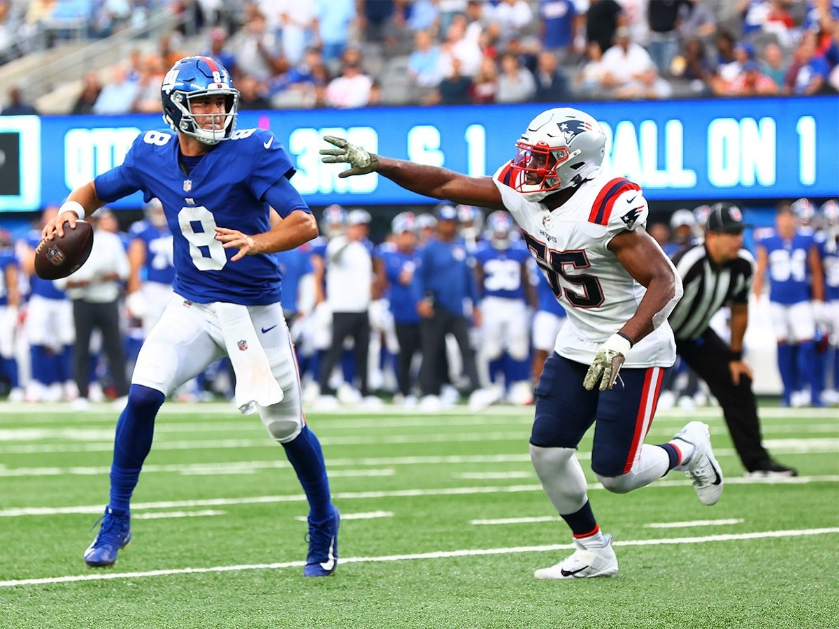 EAST RUTHERFORD, NEW JERSEY - AUGUST 29: Daniel Jones #8 of the New York Giants is pursued by Josh Uche #55 of the New England Patriots at MetLife Stadium on August 29, 2021 in East Rutherford, New Jersey. (Photo by Mike Stobe/Getty Images)