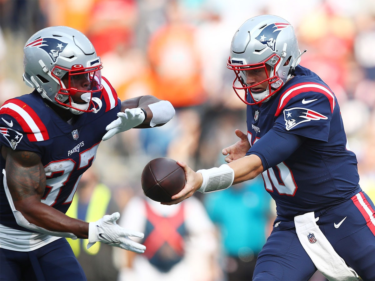 FOXBOROUGH, MASSACHUSETTS - SEPTEMBER 12: Mac Jones #10 of the New England Patriots looks to hand the ball off to Damien Harris #37 during the first half against the Miami Dolphins at Gillette Stadium on September 12, 2021 in Foxborough, Massachusetts. (Photo by Adam Glanzman/Getty Images)