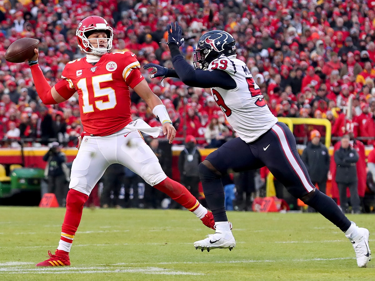 KANSAS CITY, MISSOURI - JANUARY 12: Patrick Mahomes #15 of the Kansas City Chiefs scrambles under pressure from Whitney Mercilus #59 of the Houston Texans in the second half of the AFC Divisional Round Playoff game at Arrowhead Stadium on January 12, 2020 in Kansas City, Missouri. (Photo by Tom Pennington/Getty Images)