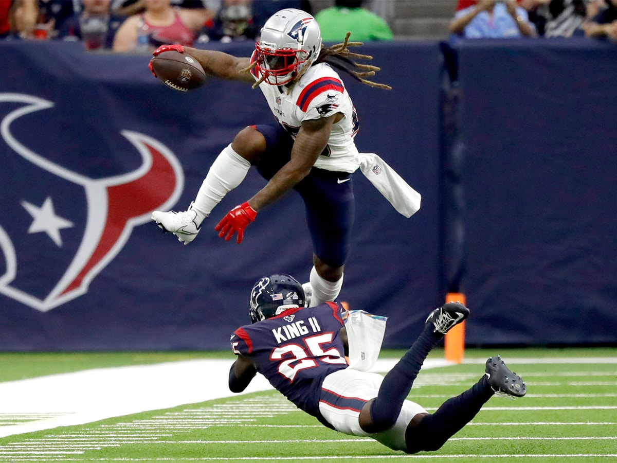 HOUSTON, TEXAS - OCTOBER 10: Brandon Bolden #25 of the New England Patriots runs with the ball as Desmond King #25 of the Houston Texans defends during the second half at NRG Stadium on October 10, 2021 in Houston, Texas. (Photo by Bob Levey/Getty Images)
